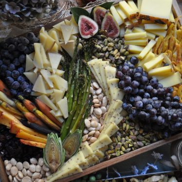 Cheese board with nuts, grapes, and asparagus